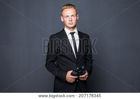 Businessman in suit looking through a binoculars with gray background poster