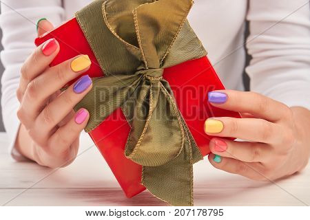 Red gift box in female hands. Beautiful box with gift in woman manicured hands close up.