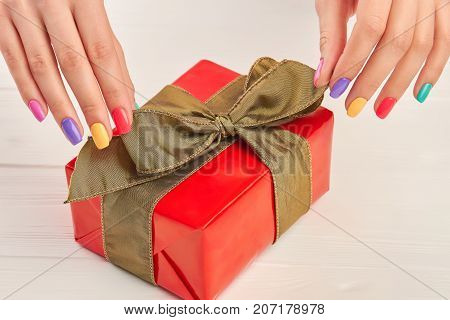 Female manicured hands and gift box. Well-groomed woman hands with colorful manicure and red gift box close up.