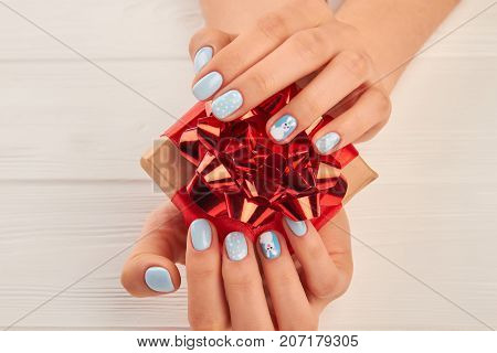 Female manicured hands holding gift box. Little gift box with red bow in woman hands with gentle winter manicure.