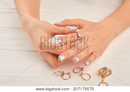 Woman hands putting on golden ring. Female manicured hands wearing golden ring with diamond. Woman well-groomed hands and jewelry.