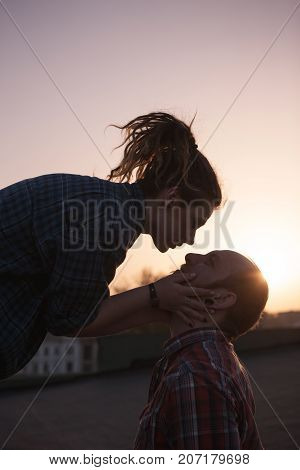 Gentle kissing couple on sunset backdrop closeup. Romantic date outdoors, hipsters in love in focus on foreground, feelings concept