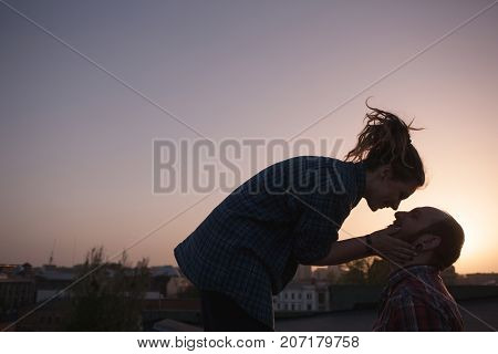 Gentle kissing couple on sunset background. Romantic date outdoors, atmospheric light with free space, focus on foreground. Happy smiling people, love concept