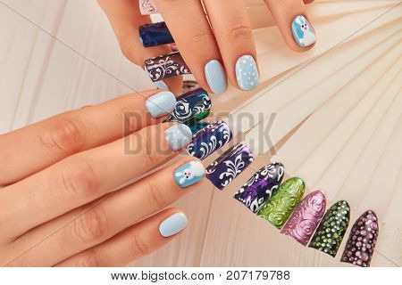 Beautiful manicure and nail art samples. Female hands with perfect winter manicure and fashion samples of nail design close up. Nail beauty salon.