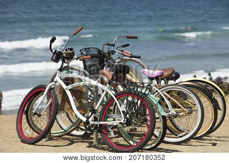 A group of two wheeled bicycles at the coast of Del Mar San Diego California.