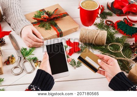 Christmas online shopping background. Cell phone screen with copy space on white wooden table, credit card and present. Mobile applications and internet commerce on winter holidays concept