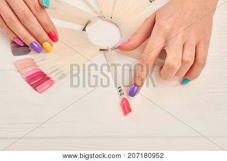 Female finger choosing nail color. Woman index finger indicating on pink color of nail color sample. Summer colors nail polish palette and female hands.