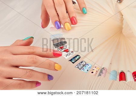Stylish manicure and nail art samples. Beautiful hands with pastel summer manicure. Nail art design palette and manicured hands close up. Nail art fashion design samples.