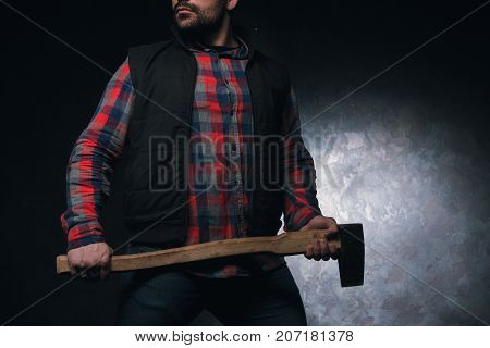Confident axeman. Armed man with axe. Dangerous unrecognizable rural man on black background closeup, protection concept