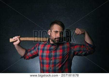 Strong woodsman with axe. Male strength. Muscular adult man on dark background, confident lumberjack portrait closeup, force concept