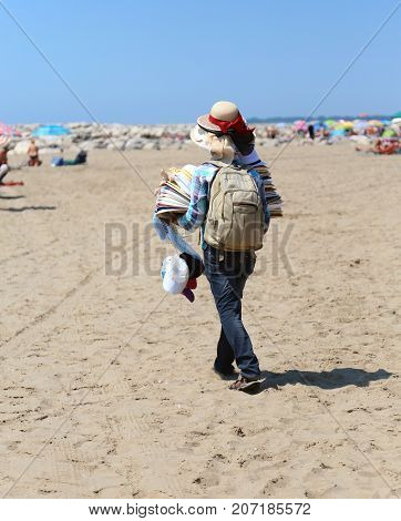 peddler sales clothes and hats on the beach in summer