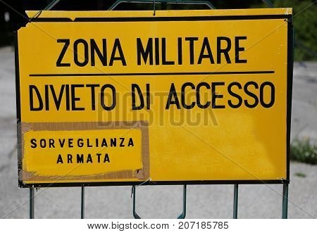 Yellow Warning sign at military zone in italy and text that means Military Area No Access. Army Surveillance