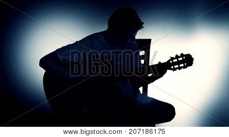 silhouette of a guitarist with an acoustic guitar sitting on a chair black background