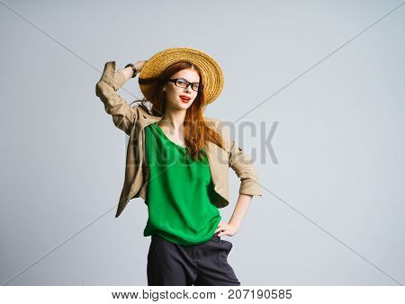 a girl with glasses and a broad-brimmed hat smiles