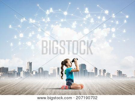 Cute kid girl sitting on wooden floor and looking in binoculars