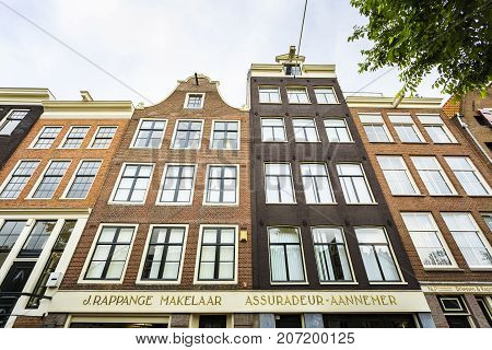 AMSTERDAM NETHERLANDS - JUNE 21 2016: A row of buildings with the iconic Amsterdam architecture in a cloudy day. Amsterdam Netherlands.