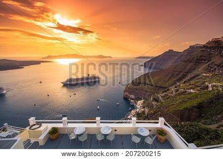 Amazing evening view of Fira, caldera, volcano of Santorini, Greece with cruise ships at sunset. Cloudy dramatic sky.
