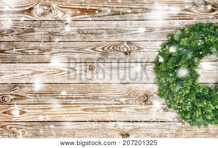 Christmas decoration evergreen wreath on rustic wooden texture. Vintage background with falling snow effect