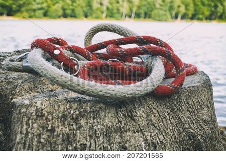 Close up rope on the stump near river and forest. Faded photo of collar of rope in autumn near lake. Red and brown rope.