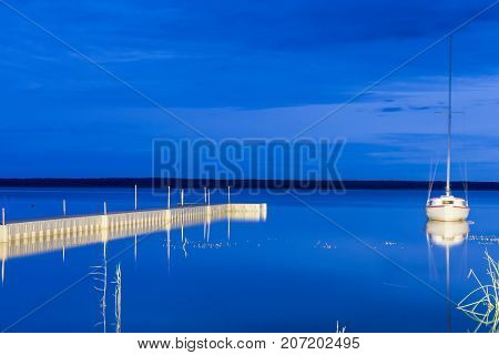Picturesque Image of Braslav Lakes in Belarus At Sunset Time. Small Sailing Boat on The Background. Taken During Blue Hour. Boat Shake Intended by Light Effect. Horizontal Image