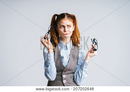 thoughtful funny girl holding two pairs of glasses in her hands, isolated