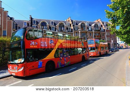 Brussels, Belgium - July 17, 2017: Red tourist buses of City Sightseeing Brussels. Famous Hop-On Hop-Off tourist buses on a sunny day in Brussels.