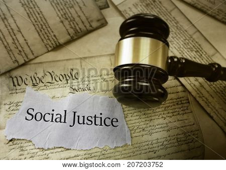 Social Justice news headline with gavel on a copy of the US Constitution
