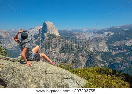 Traveler lifestyle woman looking panorama at Glacier Point in Yosemite National Park, California, USA. Wiew from Glacier Point: Half Dome, Liberty Cap, Yosemite Valley, Vernal Fall and Nevada Fall.