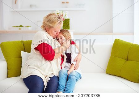 granny soothing her sad grandson at home
