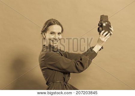 Woman retro style long dark gown taking picture with old camera vintage photo