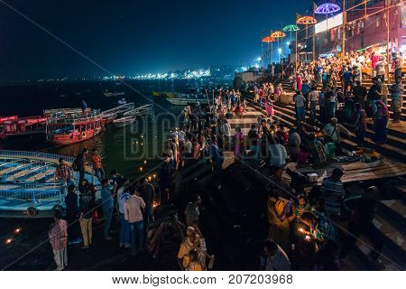 VARANASI INDIA - MARCH 13 2016: Night picture of indian Hindu people at Dashashwamedh Ghat in Ganges River after religious Ganga Aarti ritual in Varanasi India.