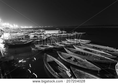 VARANASI INDIA - MARCH 13 2016: Long exposition black and white picture at night of moving boats at Dashashwamedh Ghat in Ganges River after religious Ganga Aarti ritual in Varanasi India.