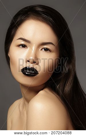 High Fashion Beauty Asian Model with bright Lip Gloss Make-up. Black Lips with gloss lipstick makeup. Long dark hair. Vertical photo poster