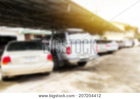 Defocused and blur image with morning sunlight of car park in outdoor parking.Copy space background for usage and any design.