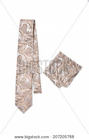 Beige paisley pattern tie and hanky on a white background