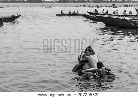 VARANASI INDIA - MARCH 14 2016: Black and white picture of Japanese man swimming with a indian child in a whale pool float at Dashashwamedh Ghat in Ganges River during day time in Varanasi India.