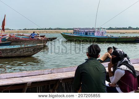 VARANASI INDIA - MARCH 14 2016: Horizontal picture of Japanese man swimming with a whale pool float while a muslim couple watch him at Dashashwamedh Ghat in Ganges River during day time in Varanasi India.