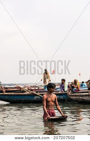VARANASI INDIA - MARCH 14 2016: Vertical picture of indian man in the holy water of Ganges River during day time in Varanasi India.
