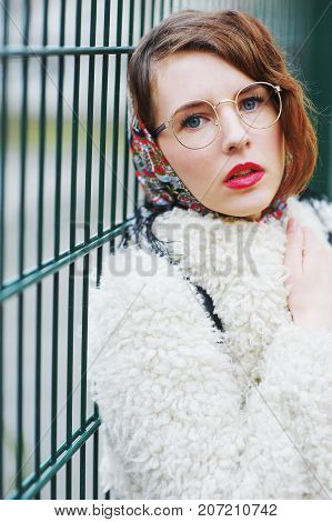 Portrait of young beautiful successful business woman with glasses in stylish clothes on the street closeup.