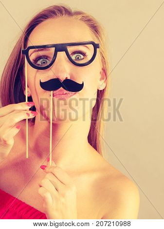 Happy woman holding fake moustache on stick having fun. Photo and carnival funny accessories concept.