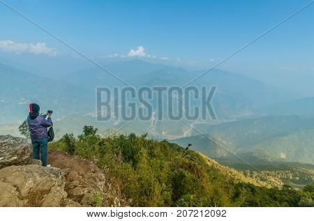 Lady taking picture at Ramitey view point - Sikkim India. From this view point twists and turns of river Tista or Teesta can be seen below River Tista flows through sikkim state
