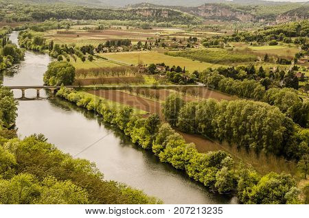 Dordogne river in the vicinity of the medieval village of Domme in the French department of Aquitaine France fields planted and mountains of calcareous rock formations common in the area.