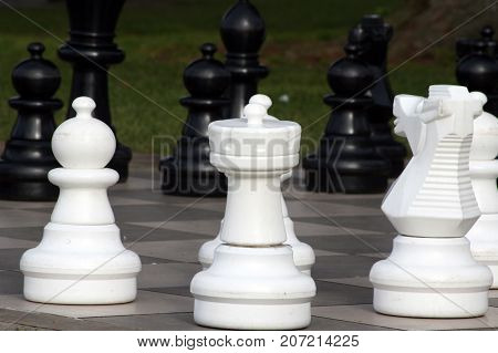 Large white rook, pawn, and horse chess pieces opposing the black chess pieces.