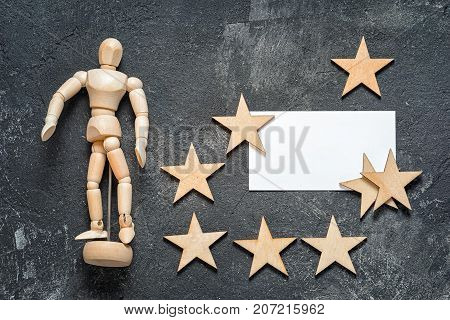 business conceptual still life with mannequin blank business card with copy space and group of wooden stars on a dark cement background top view.