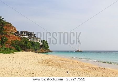 White Mansion on a cliff, along the beach of the Caribbean Sea, overlooking a catamaran with copy space in Antigua Barbuda Lesser Antilles, West Indies, Caribbean.