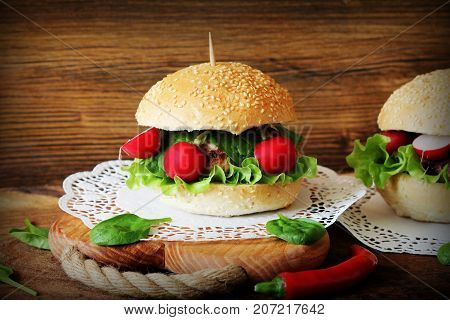 Homemade traditional burgers with beef, radish, lettuce, spinach , served on wooden background. Fast food