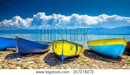 Colorful boats on the beach at the lake of Ohrid with cloudy sky, Albania. poster