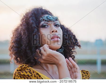 Portrait of young afro-american gypsy woman in colorful yellow traditional dress and silver crown on forehead smiling and dancing close to camera. Sexy fashion girl with curly hair