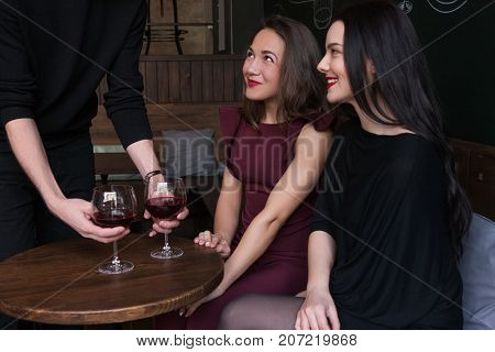Flirty mood in bar. Playful females company. Unrecognizable male with red wine, seductive smiling beautiful women, seduction concept