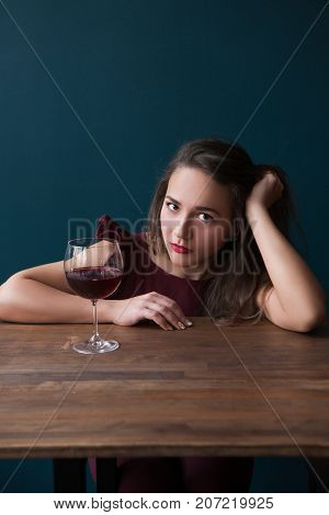 Sad young female in bar. Melancholic mood. Depressed woman with red wine on blue background with free space. Unsuccessful romantic date, problems in life, sadness concept